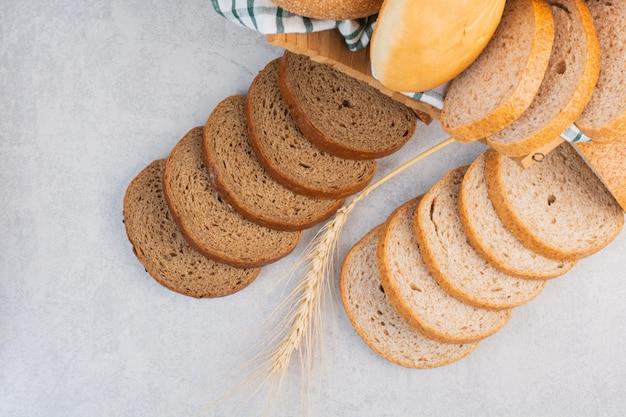 Gesneden brood op een handdoek in een doos, op het marmer.