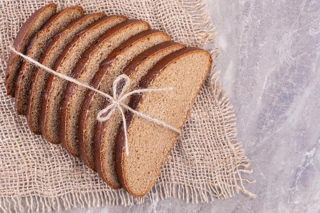 Gesneden brood op een jute, op het marmer.