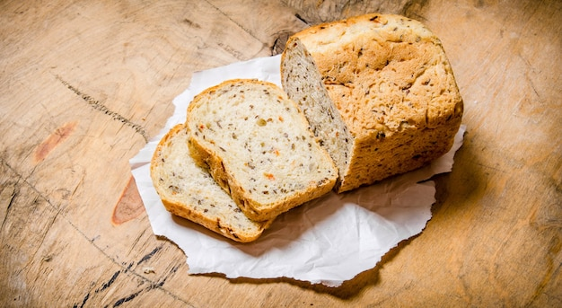 Gesneden brood op papier. op een houten tafel.