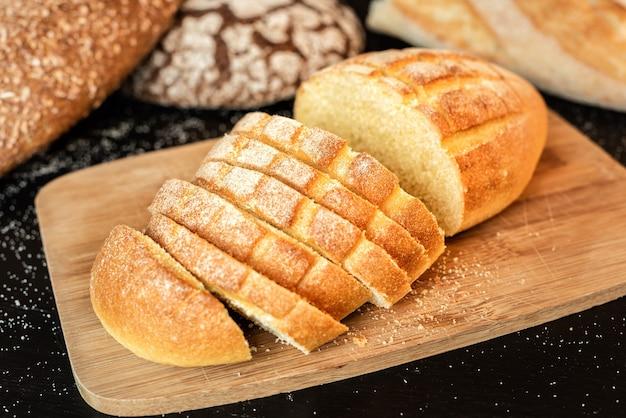 Gesneden brood op tafel op een achtergrond van verschillende soorten brood.