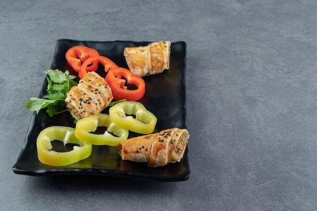 Gesneden broodje gevuld met vlees en groenten op zwarte plaat.
