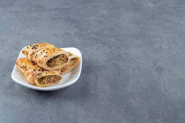 Gesneden broodje gevuld met vlees op witte plaat.