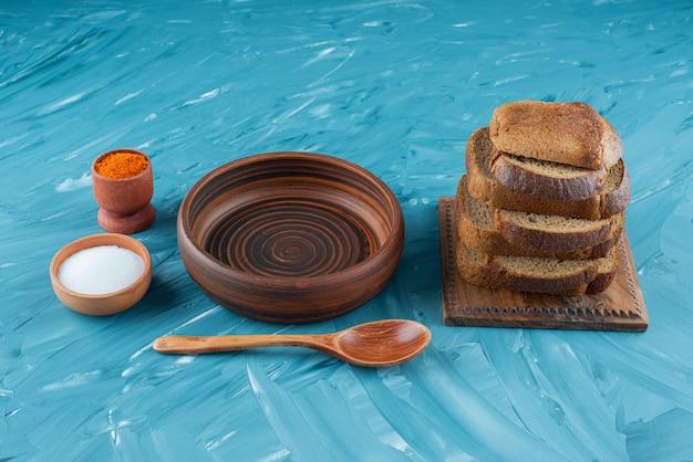 Gesneden bruin brood met zout en een lege houten lepel op een blauwe achtergrond.