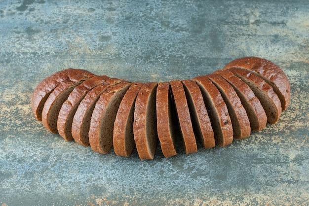 Gesneden bruin brood op marmeren achtergrond