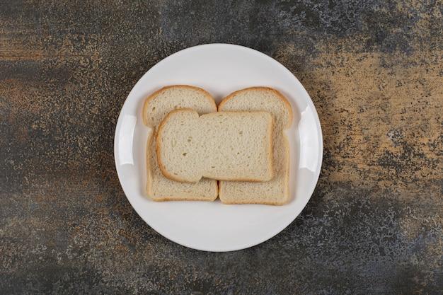 Gesneden bruin brood op witte plaat