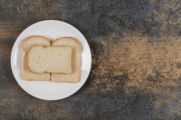Gesneden bruin brood op witte plaat.