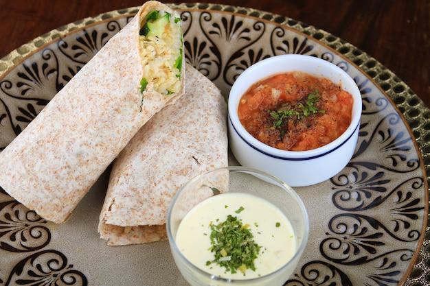 Gesneden burrito met witte en rode sauzen geserveerd in een bord met patronen