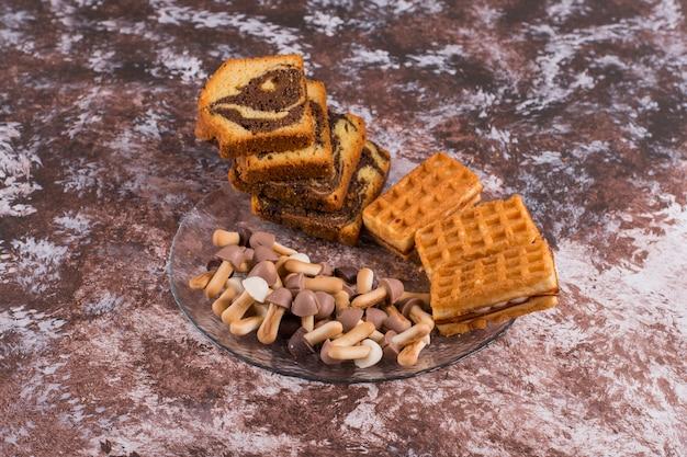 Gesneden cacaotaart met belgische wafels en koekjes in een glazen schotel