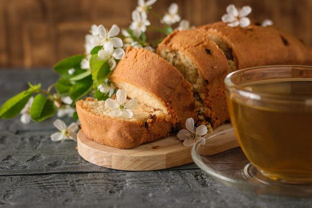 Gesneden cake met rozijnen, thee en een tak met bloemen op tafel. heerlijke zelfgemaakte taarten.