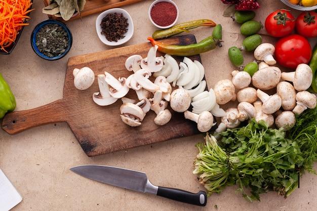 Gesneden champignons en ui op een houten tafel met groenten voor het koken van een vegetarische maaltijd