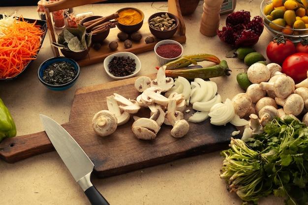 Gesneden champignons op snijplank met mes. ingrediënten bereid voor het koken van vegetarische maaltijd. gezond levensstijlconcept.