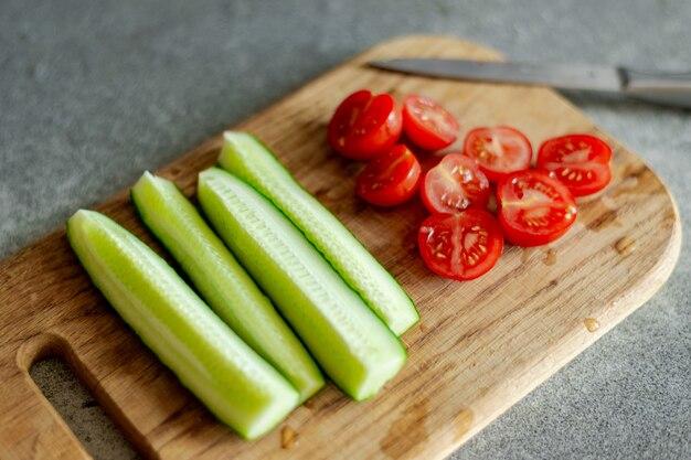 Gesneden cherrytomaatjes en komkommers op een houten bord. voorbereiding voor het koken van salade. vegetarisch eten.