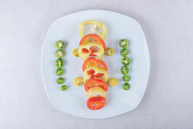 Gesneden chilipepers en paprika's op een bord op marmeren tafel.