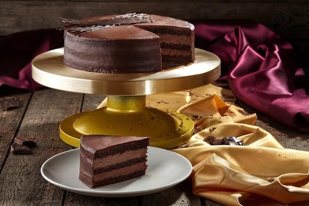 Gesneden chocoladebiscuit met botercrème gegarneerd met ganache