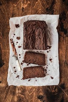 Gesneden chocoladetaart en een mes op bakpapier op donkere houten tafel, bovenaanzicht