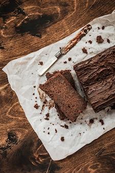 Gesneden chocoladetaart en een mes op bakpapier op donkere houten tafel