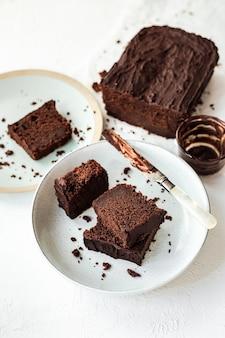 Gesneden chocoladetaart geserveerd op twee borden, een mes bedekt met chocolade