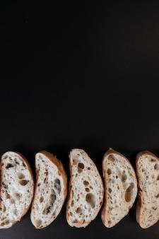 Gesneden ciabattabrood op zwarte achtergrond. italiaans witbrood. bovenaanzicht met kopie ruimte.
