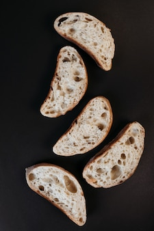 Gesneden ciabattabrood op zwarte achtergrond. italiaans witbrood. bovenaanzicht.