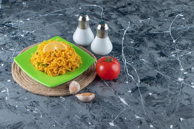 Gesneden citroen en noedels op een bord op een onderzetter naast tomaten, zout en knoflook, op de marmeren achtergrond.