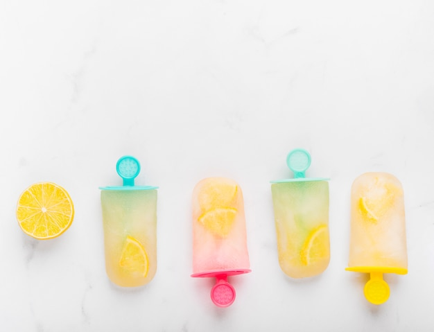 Gesneden citroen en verse ijsijslolly met citrusvrucht op kleurrijke stokken