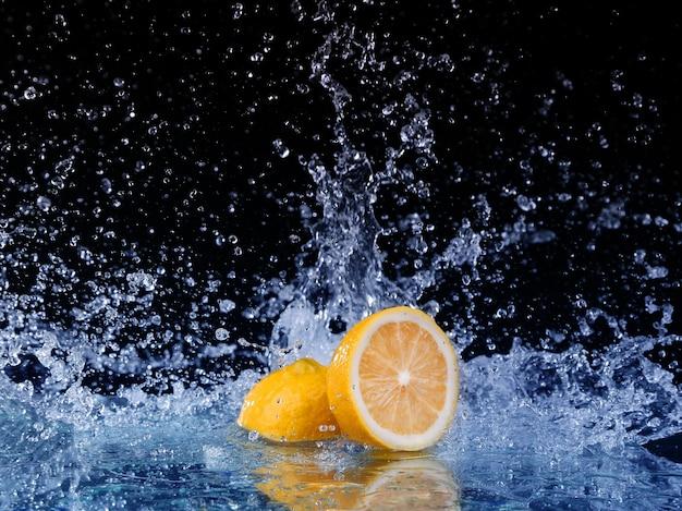 Gesneden citroen in het water op zwarte achtergrond