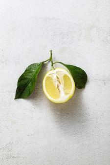Gesneden citroen op een witte stenen tafel met bladeren.