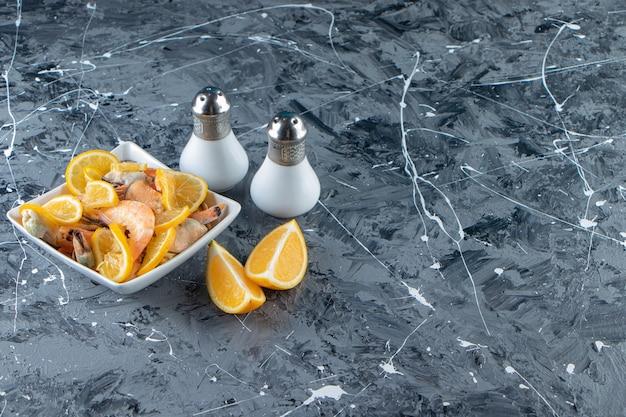 Gesneden citroenen en garnalen in een kom naast zout, op de marmeren achtergrond.