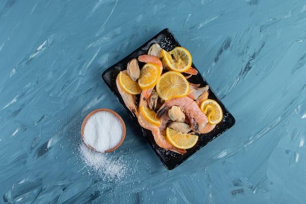 Gesneden citroenen en garnalen op een schotel naast zoutkom, op het marmeren oppervlak.