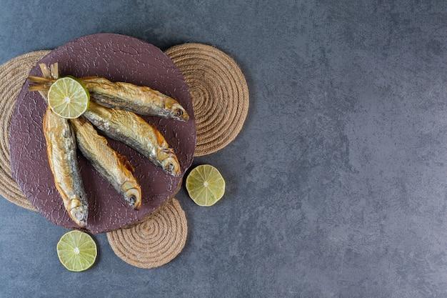 Gesneden citroenen en gedroogde gezouten vis op een bord op een onderzetter, op het marmeren oppervlak
