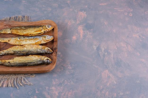 Gesneden citroenen en gezouten vis op een snijplank op een jute servet, op het marmeren oppervlak