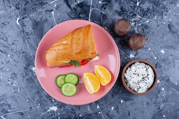 Gesneden citroenen en komkommer, sandwich op een bord naast een kom kaas, op het blauw.