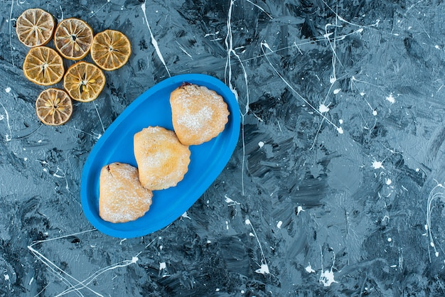 Gesneden citroenen naast taarten op houten plaat, op de blauwe tafel.