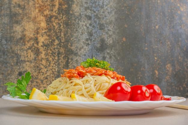 Gesneden citroenen, tomaten, peterselie en noedels op een bord, op het marmeren oppervlak