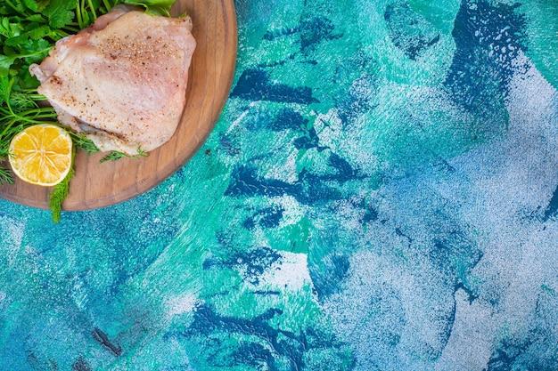 Gesneden citroenen, ui en peterselie met kippenvlees op een plank