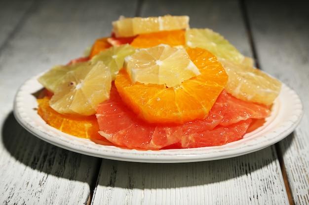 Gesneden citrusvruchten op plaat, op houten tafel