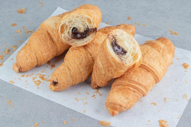 Gesneden croissants op pape, r op de marmeren achtergrond. hoge kwaliteit foto