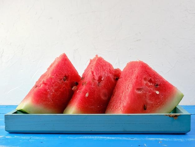 Gesneden driehoeken rijpe rode ronde watermeloen met zaden