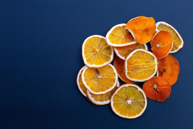 Gesneden droge sinaasappelen op blauw.