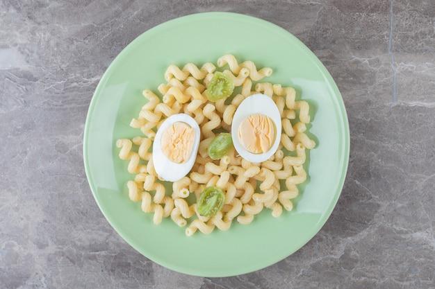 Gesneden eieren en macaroni op groene plaat.