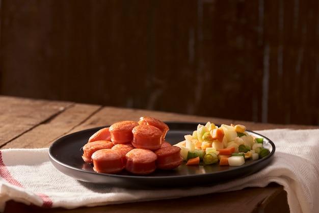 Gesneden en gebakken worst met salade van bovenaf gezien close
