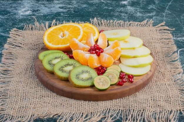Gesneden en gehakte fruitsalade in een schotel op blauwe ondergrond.