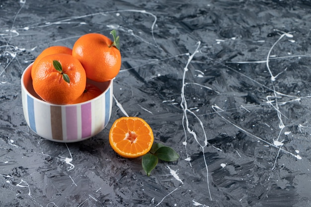 Gesneden en geheel vers oranje fruit met bladeren die op kleurrijke kom worden geplaatst.