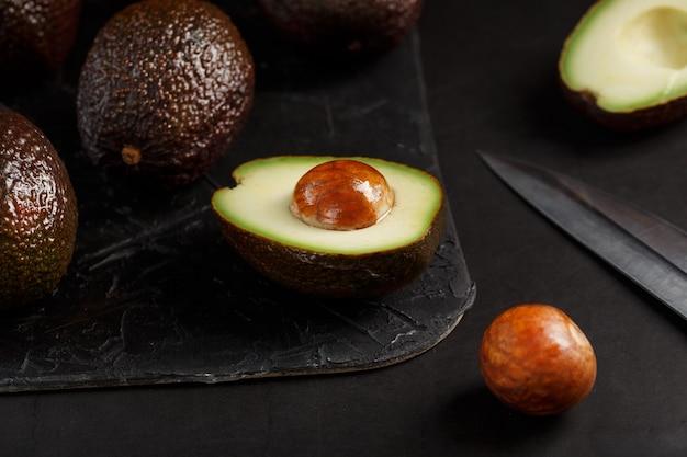 Gesneden en hele biologische avocado hass met een mes op een zwarte ondergrond