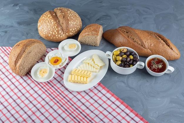 Gesneden en hele broodbroden rond een ontbijtopstelling op tafellaken op marmeren tafel.