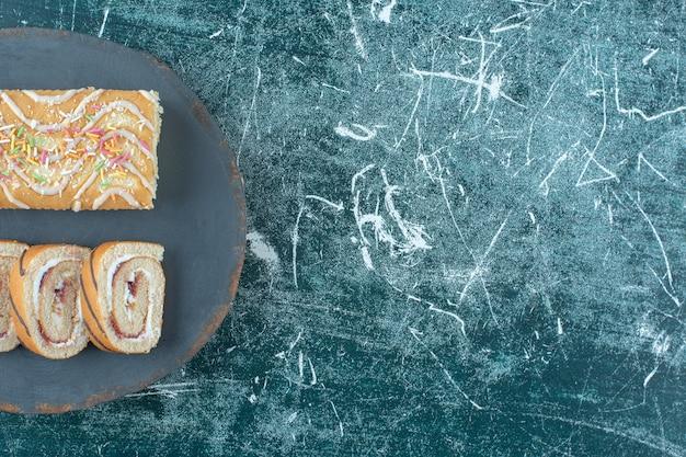 Gesneden en hele broodjescakes op een bord, op de blauwe achtergrond. hoge kwaliteit foto