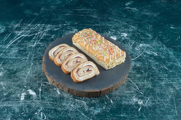 Gesneden en hele broodjescakes op een bord, op het blauwe oppervlak