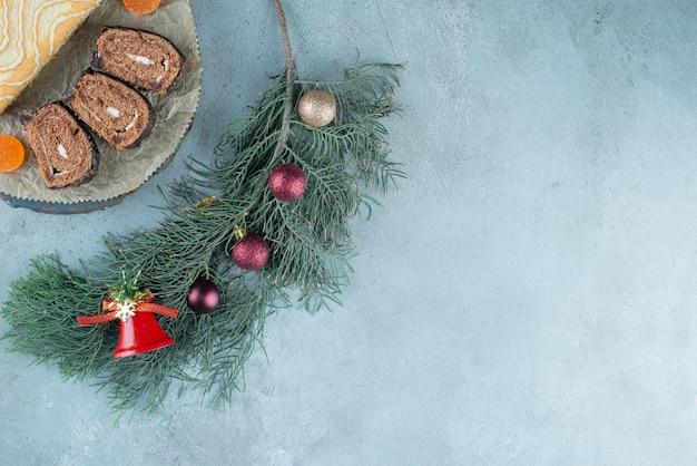 Gesneden en hele cakerol op een schotel met een versierde dennentak op marmer.