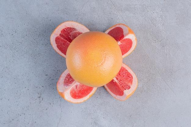 Gesneden en hele grapefruits weergegeven op marmeren achtergrond.