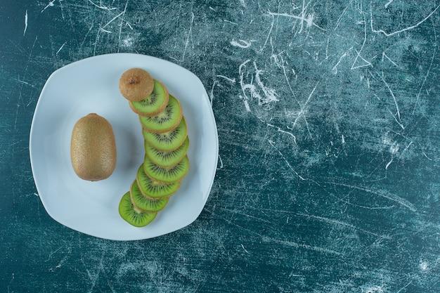 Gesneden en hele kiwi op plaat, op de marmeren tafel.